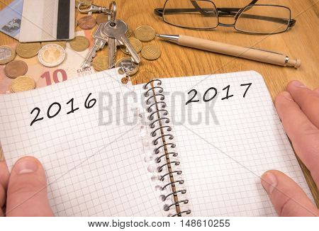 New year concept for 2017 - A man's hands tears a page from a notebook with the year 2016 written remaining the page with the 2017 year. Financial elements in the background and copy space.
