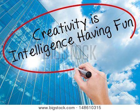 Man Hand Writing Creativity Is Intelligence Having Fun With Black Marker On Visual Screen
