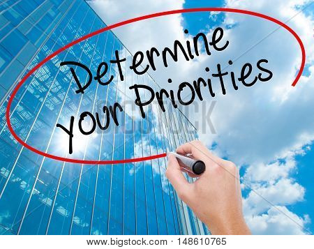 Man Hand Writing Determine Your Priorities With Black Marker On Visual Screen
