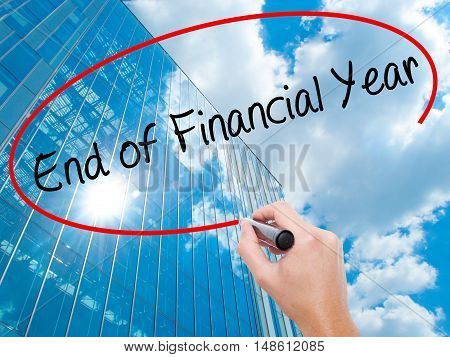 Man Hand Writing End Of Financial Year With Black Marker On Visual Screen