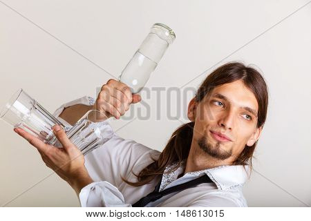 Drinking party liquor flair bartending concept. Bartender fills glass from bottle. Male tapster pours alcohol into glass.