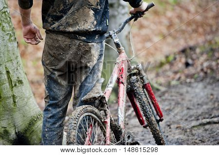 Mountainbiker and bike dirty with mud and water