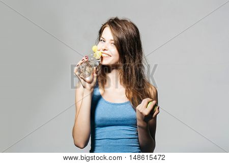 Beautiful girl with long hair in blue undershirt with apple drinks water from bottle on grey wall