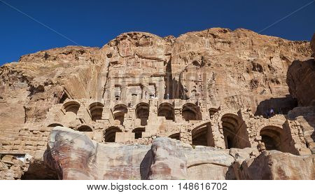 PETRA JORDAN - OCTOBER 28 2014: Unidentified tourists near Urn Tomb one of the best preserved tombs hewn into the sandstone cliff.