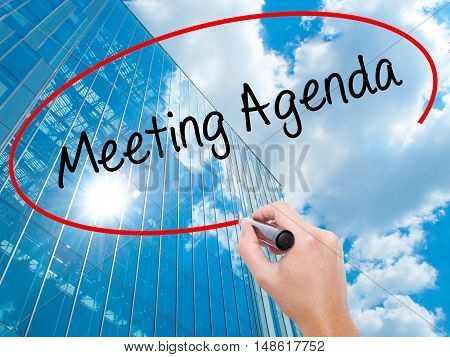 Man Hand Writing Meeting Agenda  With Black Marker On Visual Screen