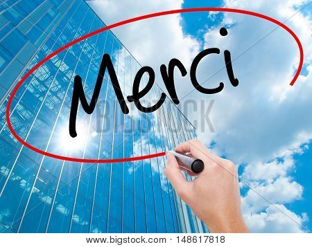 Man Hand Writing Merci  (thank You In French) With Black Marker On Visual Screen.