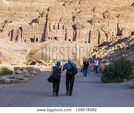 PETRA JORDAN - OCTOBER 28 2014: Unidentified locals and tourists on colonnaded street with urn silk and royal tombs on background.