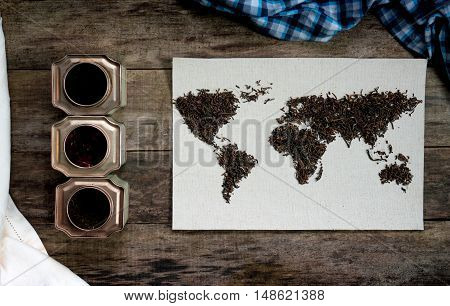 map of the world, lined with tea leaves on old paper. Eurasia, America, Australia, Africa. vintage. green tea on rustic wooden table