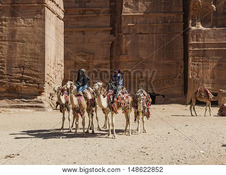 PETRA JORDAN - OCTOBER 29 2014: Unidentified local Bedouin guided on camels near Royal tombs.