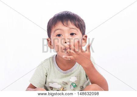 cute little boy licking fingers while eating sweetsfocus fingers