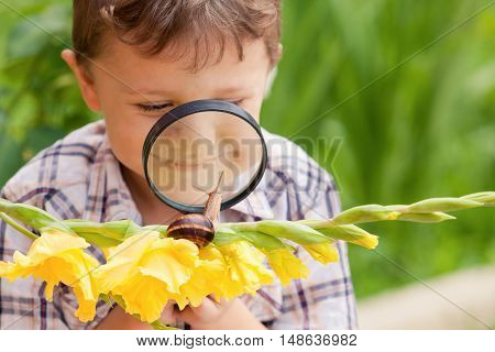 Happy little boy playing in the park with snail at the day time. He having fun on the garden. Concept of the kid is ready to go to school.