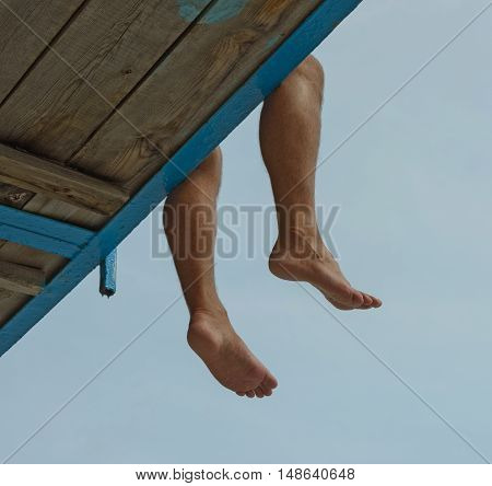 Underside view of dangling legs with bare feet of man that sitting on the edge of wooden board-walk on metal joists painted blue.