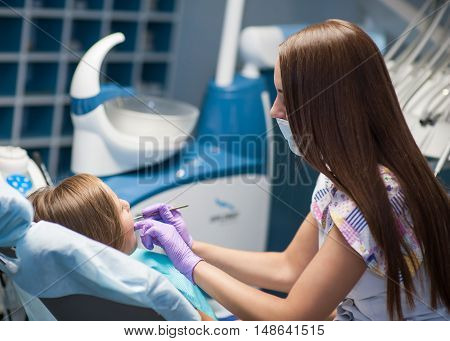 Dentist curing a child patient in the dental office in a pleasant environment. There are specialized equipment to treat all types of dental diseases in the office.