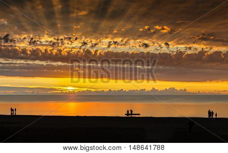 Happy people walking during sunset at a beach of Jurmala - famous international Baltic resort in Latvia, Europe