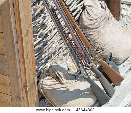 three muzzle loading firearm standing at the wall of the trench