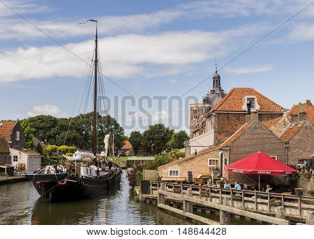 Enkhuizen The Netherlands - August 9 2016: Ship in the harbor of Enkhuizen with old houses drommedaris and terrace with people.