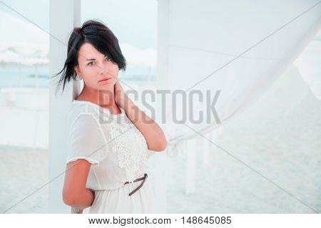 Woman, Brunette With Short Hair In White Dress On The Beach Of Ocean, Sea Near Sun Shade, Tent. Vaca