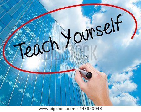 Man Hand Writing Teach Yourself  With Black Marker On Visual Screen