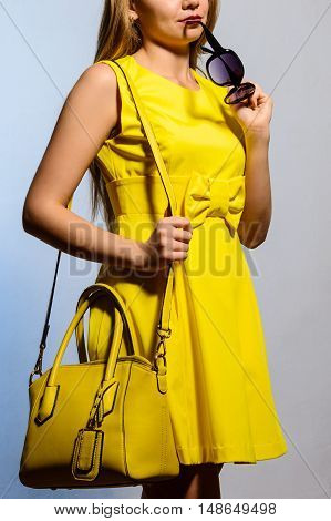 Fashionable young woman in a yellow dress with handbag over her shoulder
