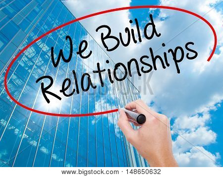 Man Hand Writing We Build Relationships With Black Marker On Visual Screen