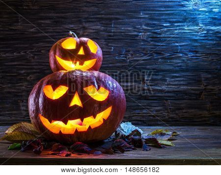 Grinning pumpkin lantern or jack-o'-lantern is one of the symbols of Halloween. Halloween attribute. Wooden background. poster