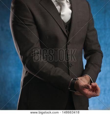 Business man adjusting his sleeve on a blue background stock picture