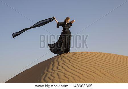 woman in traditional emirati dress (abaya) in Liwa desert