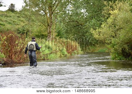 Back view of fly-fisherman fishing in river