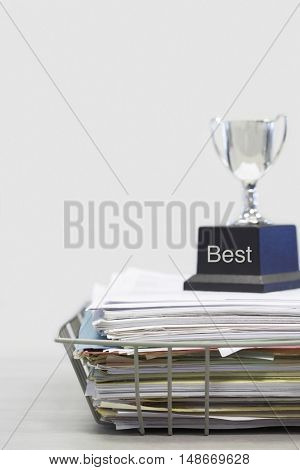 Trophy on Top of Papers saying best