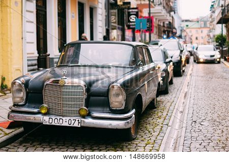 Batumi, Georgia - May 28, 2016: The Black Rarity Retro Mercedes Benz Car Parked On The Narrow Paved Street In A Row With Another Modern Automobiles In Summer Daytime.