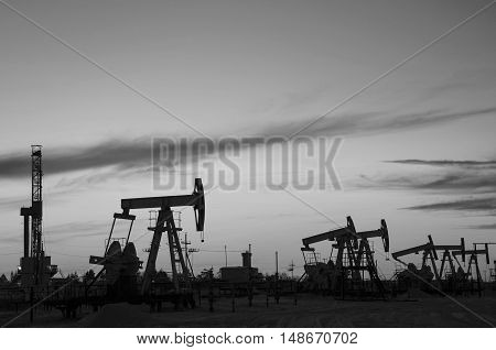 Pump jacks and derrick silhouette during sunset in the oilfield. Oil and gas concept. Black and white.