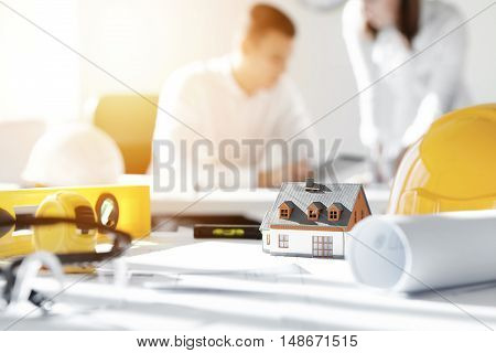Selective Focus. Close Up Shot Of Scale Model House On Table With Yellow Helmets And Engineering Too