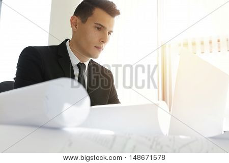 Handsome Serious Caucasian Contractor In Suit Working On Laptop Computer, Sitting At Desk With Bluep
