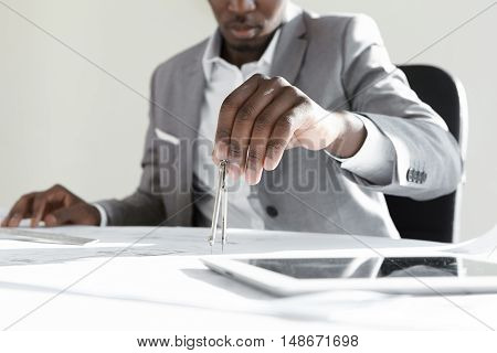 African engineer using technical drawing tool for calculating measurements of housing project. Black contractor holding compass working on drawings sitting at desk with blueprints and touch pad