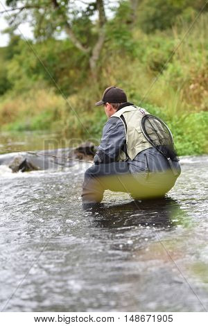 Fly-fisherman fishing in river