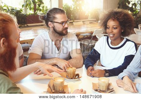 Young Hipster Dark-skinned Woman With Curly Hair Explaining Vision And Sharing Ideas With Her Busine