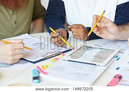Team Of Creative Young People Holding Pencils While Discussing Business Strategy And Plans Of Their