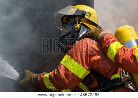 fireman in fire fighting suit spraying water to fire surround with smoke and drizzle close up