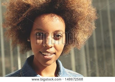Flare Sun. Attractive Fashionable Black Student Girl With Facial Piercing Looking At Camera With Hap