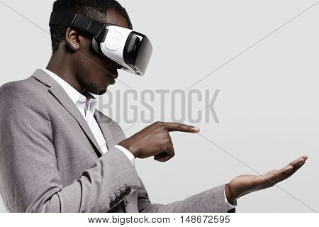 Dark-skinned Man In Formal Wear With Virtual Reality Headset For Smart Phone On His Head, Playing Vi