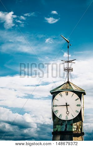Oslo, Norway. Close View Of Top Part With Big Clock And Steeple Of Old Lighthouse At Aker Brygge District. Dramatic Blue Cloudy Sky Background