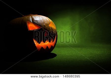 The Carved Face Of Pumpkin Glowing On Halloween On Green Background