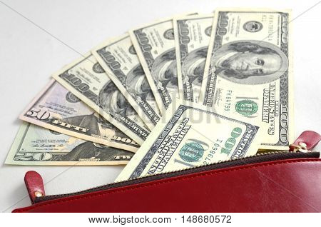 Several dollar bills in a red woman's purse