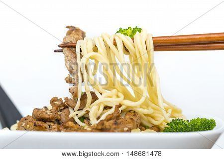 Eating Stirfried pork and Ramen style noodle soup with chopsticks