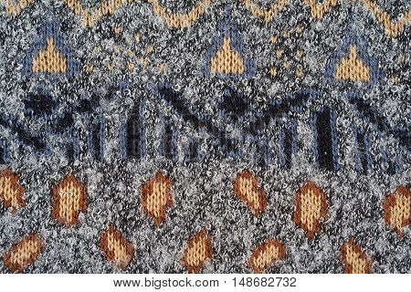 Part of blue knitted sweater with samplers as a background