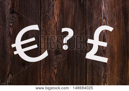 Paper currency signs, Pound Sterling VS Euro. Abstract conceptual image. Wooden background