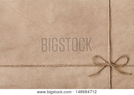 String or twine tied in a bow on kraft paper texture. New Year or Christmas gift or present concept.