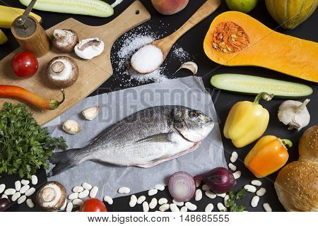 Food ingredients and aurata fish on black background
