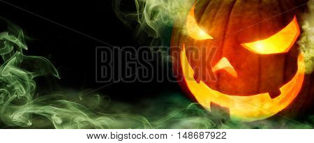 Jack o lantern with evil glowing eyes emanating green smoke on black panoramic background with copyspace