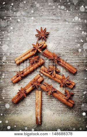 Christmas or New Year card with fir tree made from spices cinnamon sticks, anise star and cane sugar on rustic wooden background. Magic snow effect, vintage toned, top view.